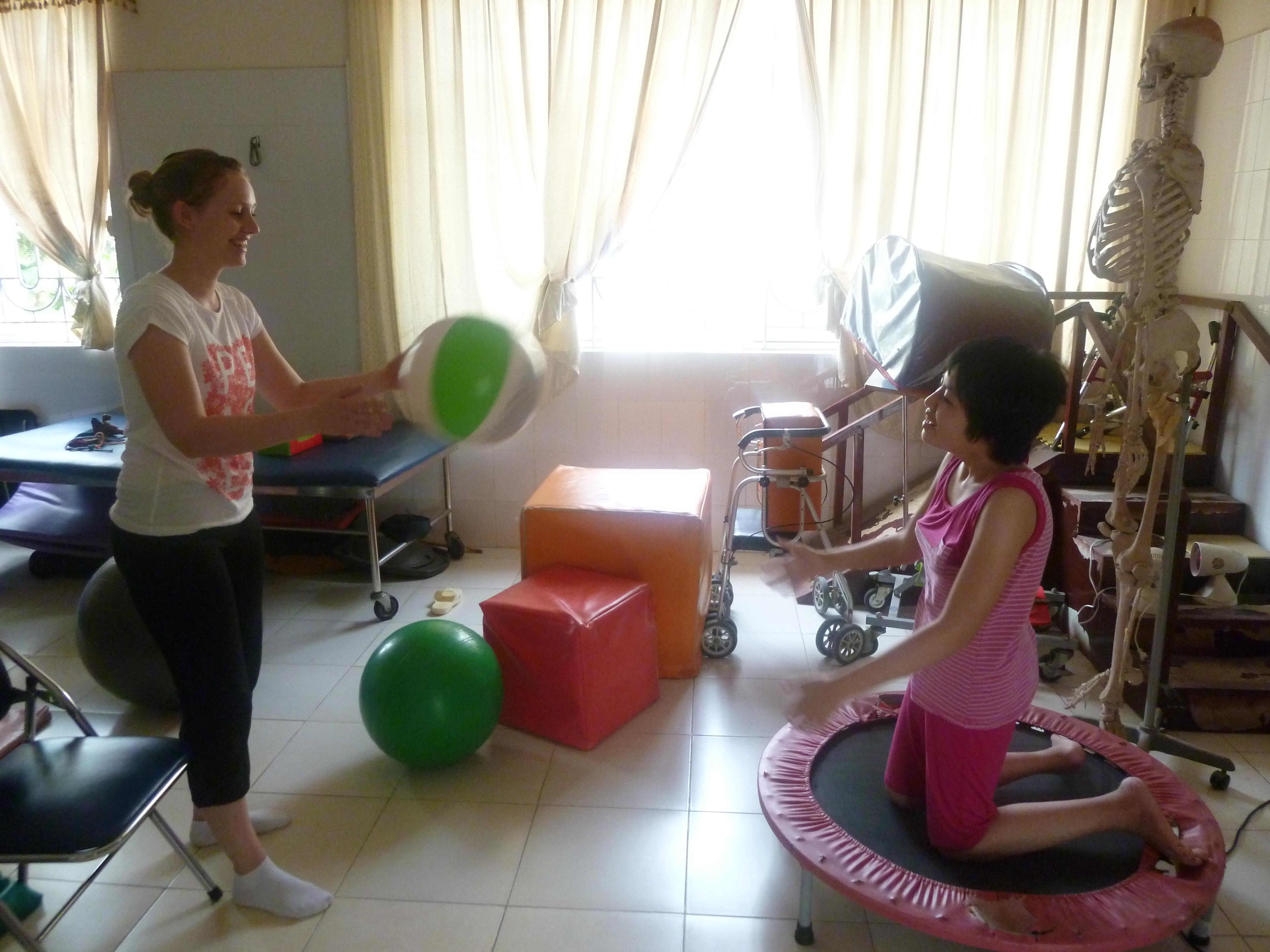 Female intern with Projects Abroad participating in sensory play with a child during her physiotherapy internship in Vietnam.